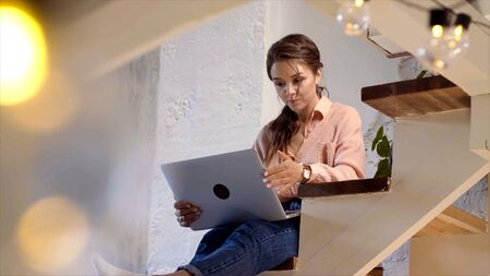 Girl using her laptop in her house. Stock footage. Young woman working at laptop at home Stockfoto