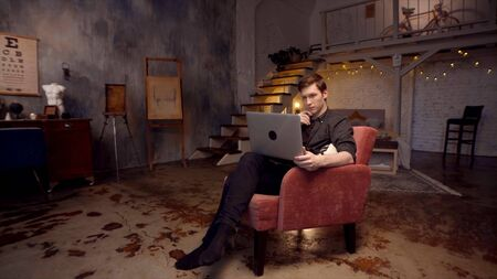 Young man is working at laptop sitting on couch. Stock footage. Young freelancer is working intently at laptop