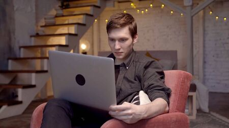 Young man is working at laptop sitting on couch. Stock footage. Young freelancer is working intently at laptop Stockfoto - 133566376