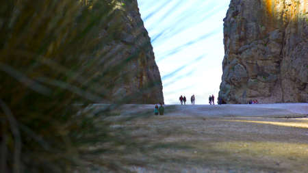 People walking between two giant mountains on bright sky background, view from behind the grass leaves. Gap between two rock walls in a gorge.