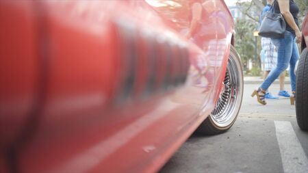 An American classic car is shown. Action. Part of the red car with a wheel