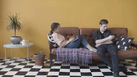 Young couple sitting at home on couch, addicted and obsessed with modern gadgets. Stock footage. Man using mobile phone while girlfriend overusing laptop, avoiding ignoring each other.