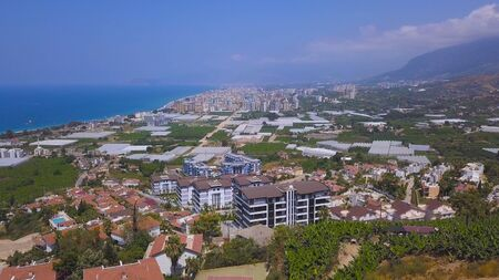 Aerial view of beautiful hills leading down to coast and azure sea and the beach. Small green coastal town is the most popular travel holiday destination in Europe.