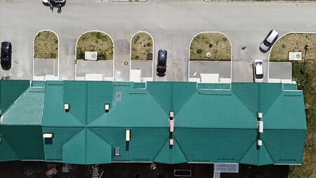 Aerial view of the bright turquoise roof od the building with parked cars near the decorative flower beds. Stock footage. 90 degrees top view of parking with cars near the house under the summer sun.