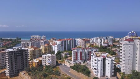 Breathtaking view of summer landscape with the city in Turkey by the sea. Many high buildings and residential houses in front of blue endless sea.
