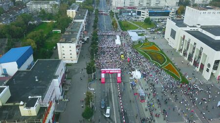Aerial view from drone on crowd of people who is starting their run on marathon event. Top view of many people gathered in the street before running the marathon.