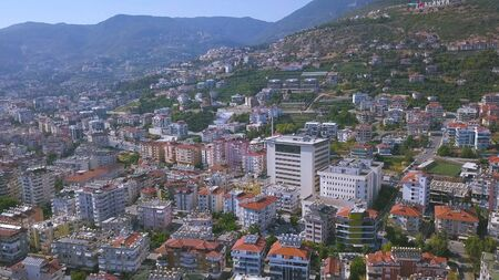 Flying over sunny town Alanya in Turkey located by the Mediterranean sea. Aerial view of the mountain slope covered by houses and trees.