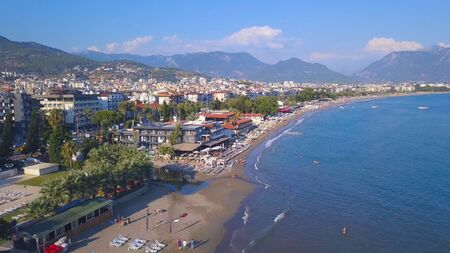 Aerial view of the beautifull beach in Spain. View from drone flying above the sea shore with many people swimming and having fun in blue water. Stock fotó