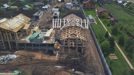 New home wooden construction from above in countryside area. Aerial view of summer green village and a new wooden log house. Stock fotó