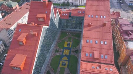 Aerial view of new school building in residential area, architecture concept. Top view of the pink roof a high building with a small court.