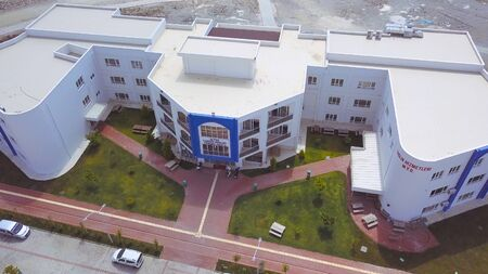 Aerial view of beautiful white building of University Campus, surrounded by green lawn and footpath, education concept. Top view of university in Turkey with many cars parked nearby.