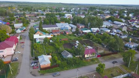 Aerial view of the modern village with cute houses and green fields. Flying along the street of the village on a summer sunny day.