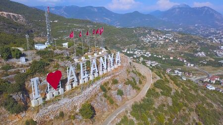 Turkish flags in a row and the inscription I love Alanya on the slope of a mountain, tourism concept. Wonderful country from a height with green vegetation and roofs of buildings. Stock fotó