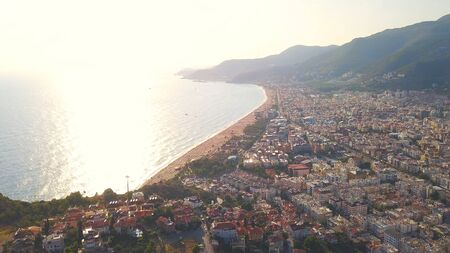 Aerial view flying towards the city and a mountain against the sunset above the sea. Amazing seascape with sunlight reflected in the water surface.