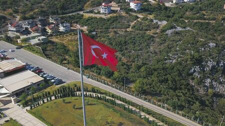 Flying around the red waving Turkish flag on green forested mountains background. Aerial of the observation deck on a mountain slope.
