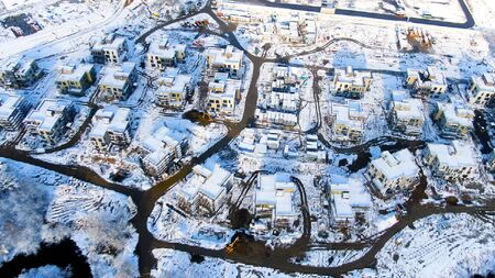 Aerial view of winter industrial cityscape from air. Snowy landscape at cold season of a town in forested area, snow scenery landmark. Stock fotó