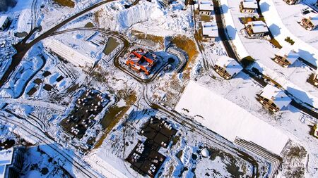 Flying over the industrial area of the city covered by snow on a sunny winter day. Aerial of beautiful houses and the construction site in winter time.