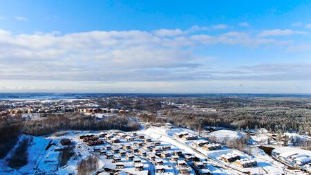 Aerial view of winter skyline, industrial cityscape from air. Snowy landscape at cold season of a town in forested area, snow scenery landmark.