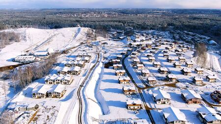 Flying over the residential area of the city covered by snow on a sunny winter day. Aerial of beautiful houses in winter time located near the forest. Stock fotó
