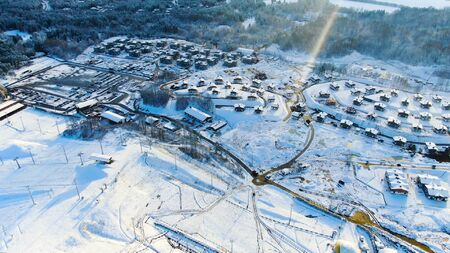 Aerial view of small village among the fields and forests in winter. Winter picturesque landscape, snow covered field and trees in countryside.