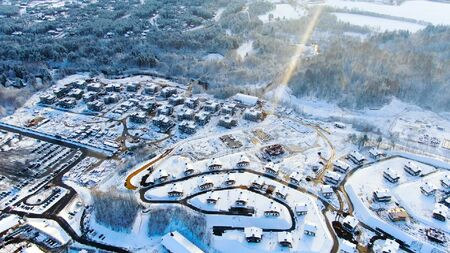 River flows near small village in winter, aerial landscape, cold weather concept. Breathtaking view of cold countryside area near coniferous forest.