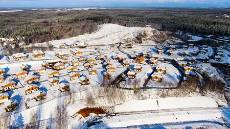Aerial view of winter village near the pine tree forest. Amazing flight above houses and cottages covered by snow located in ecological area.