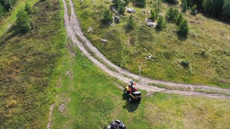 Group travels on ATVs and UTVs on the nature. Footage. Top view of people riding Quad bikes in nature