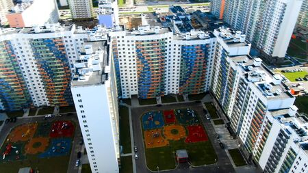 Modern glass skyscrapers apartment of white color with colorful curved lines on the facade. Motion. Aerial view of tall houses with exterior and outdoor facilities. Stock Photo