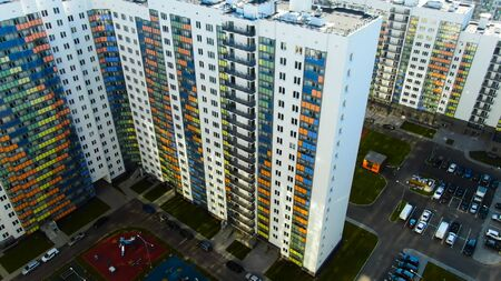 Flying over the residential houses with bright colorful facadesin a summertime. Aerial of the white buildings and inner yard with parked cars.