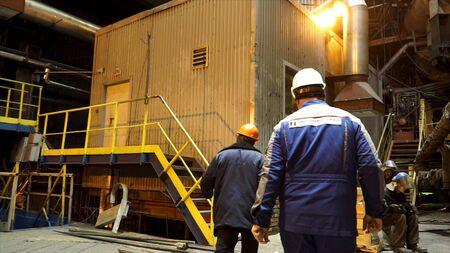 Vue arrière de métallurgistes marchant à l'intérieur de l'atelier chaud de l'usine de production métallurgique. Concept de l'industrie lourde, travailleurs de l'usine. Banque d'images