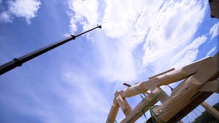 Bottom view of new frame energy efficient house and the crane on blue cloudy sky background. Wooden building frame at the construction site.