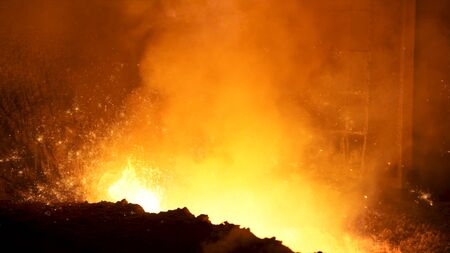 Close up of liquid metal in hot workshop of the metallurgical plant. Stock footage. Flying sparkles inside the furnace, heavy industry concept.