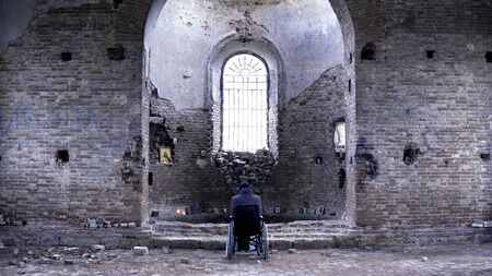 Man in a wheelchair in a ruined Church. Footage. Back view of a man in an abandoned Church. The concept of memories.