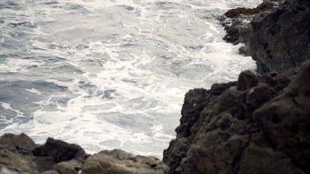 The waves fighting about the rocky ocean coast. Action. View of the raging waves of the sea breaking on the rocks.