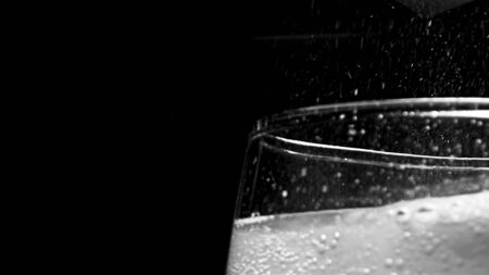Glass with hissing carbonated bubbles. Stock footage. Close-up of carbonated foam bubbling and sizzling formed to edge of glass on black isolated background
