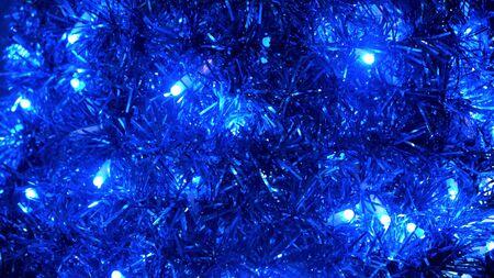 Festlicher heller Weihnachtshintergrund aus Girlande und blinkenden Glühbirnen. Konzept. Nahaufnahme von Neujahr blaues Lametta, Heimtextilien.