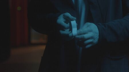 Close-up of man bandaging his fingers. Stock footage. Men's hands are sealed with plaster hands. Bandit in coat puts plaster on his fingers before fight on dark street background. Foto de archivo