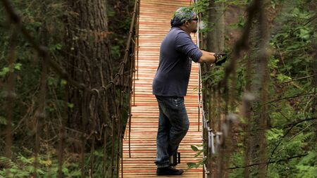 Side view of a man standing and having a rest on the wooden suspension bridge. Stock footage. Man looking into the distance and smoking a pipe in the forest.