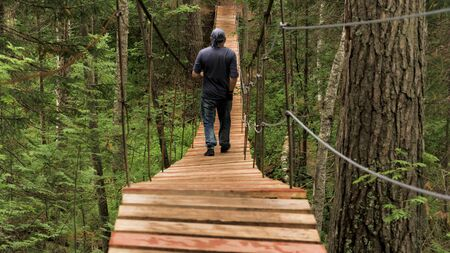 Rear view of male tourist crossing wooden suspension bridge in green forest. Stock footage. Back view of a man walking on the wooden bridge among summer green trees, active lifestyle concept.