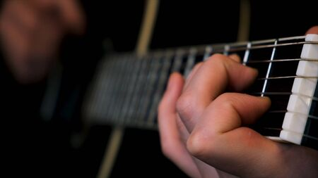 Close up of man hands masterly playing chords. Musician plaing acoustic guitar, composing music in rock genre.