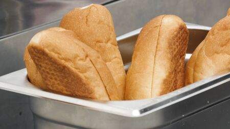 Close up of freshly baked bread buns inside metal metal container. Stock footage. Tasty soft bread for making sandwiches, flour products concept. Banco de Imagens