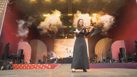 Yekaterinburg, Russia-August, 2019: Beautiful young woman playing violin on stage. Action. Violinist plays beautifully on citys open stage during festival 新聞圖片
