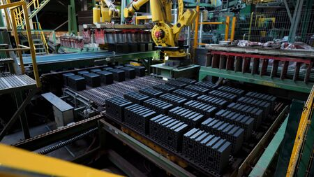 Raw ceramic blocks being transported automatically by professional machinery at the manufacturing plant. Rows of ceramic blocks on a conveyor belt at the factory.