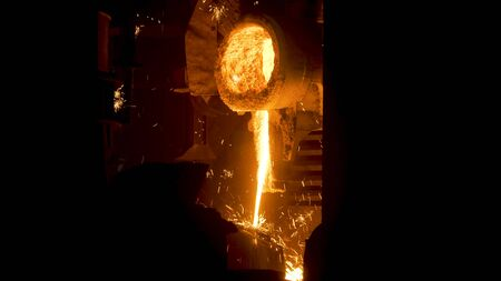 Smelting works at plant. Scene. Jet of alloy is poured out and sparks are carried in different directions at smelter. Bright hot stream of alloy flows and sparkles. Фото со стока