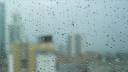 Close up of a glass window on a rainy day with big drops on blurred city ang grey heavy sky background. Stock footage. Transparent water drops on a vertical glass surface.