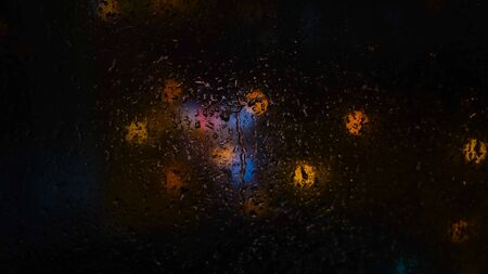 Close-up of raindrops on glass on background of blurred lights in dark. Concept. Blurred lights outside window when it rains at night.