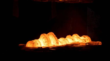 Steel quenching at high temperature in industrial furnace at the workshop of a forge plant. Process of cooling, heat treatmen, blacksmith and metallurgical industry, steelmaking.