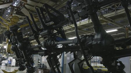 Production process of heavy mining trucks at the factory. Dump truck transmissionon the Industrial conveyor in the workshop of an automobile plant.