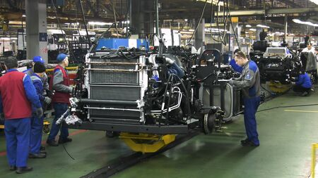 View inside of the car assembling plant and workers at the production line. Industrial workshop and assembly line for the production of commecical and military trucks, wheel chassis and vehicles.