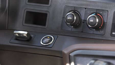 Interior of a modern car, driver starting the engine by pressing the button. Close up of a male hand pushing the car starting button inside luxury vehicle.